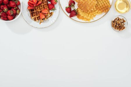 top view of waffles and strawberries on plated near bowls with honey and nuts on white