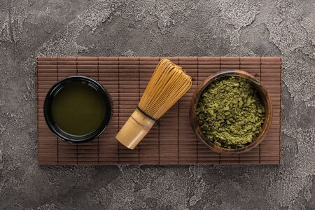 top view of matcha tea with whisk on bamboo mat on dark stone table