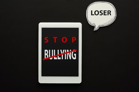 top view of digital tablet with stop bullying lettering on screen on black background near white speech bubble with loser word