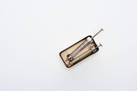 top view of aged syringes in vintage box on white background with copy space Stock fotó