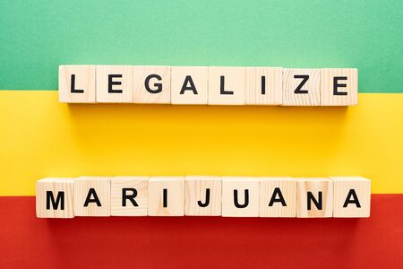 top view of wooden blocks with legalize marijuana lettering on Rastafarian flag Stock Photo