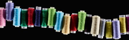 panoramic shot of bright and colorful threads isolated on black Фото со стока