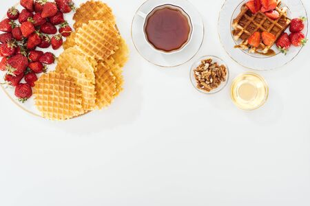 top view of waffles, strawberries, honey, nuts and tea on white