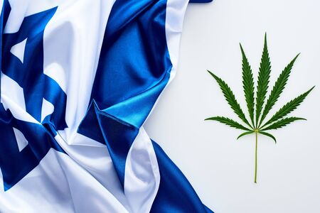 top view of green cannabis leaf near flag of Israel on white background