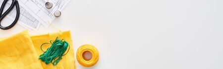 panoramic shot of scissors, thimbles, thread, knitting yarn ball, fabric and sewing patterns on white background