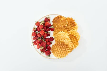 top view of big plate with strawberries and waffles on white