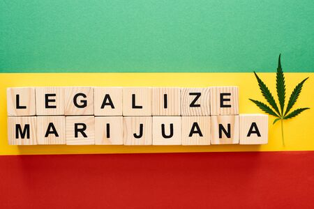 top view of cannabis leaf and wooden blocks with legalize marijuana lettering on Rastafarian flag