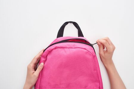 Partial view of schoolgirl zipping bright pink schoolbag isolated on white
