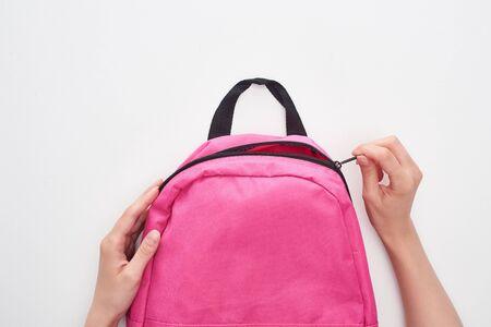 Teilansicht eines Schulmädchens, das eine hellrosa Schultasche isoliert auf weiß reißt