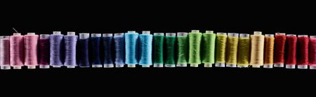 panoramic shot of bright and colorful threads isolated on black Stock Photo