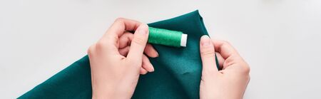 panoramic shot of seamstress holding colorful fabric and thread on white background Stock Photo