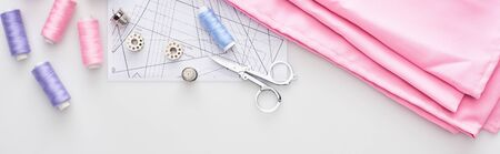 panoramic shot of fabric, sewing pattern, scissors, thimbles, bobbins and threads on white background Imagens