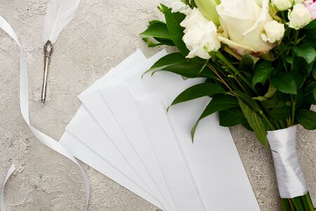 top view of envelopes near bouquet, white ribbon and quill pen on grey textured surface 版權商用圖片