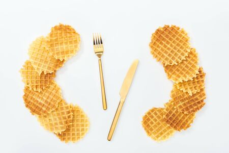 top view of cutlery rounded by waffles on white