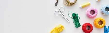 panoramic shot of zipper, scissors, threads, knitting yarn balls, tracing wheel, measuring tape on white background Фото со стока