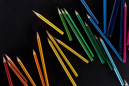 Scattered sharpened color pencils isolated on black