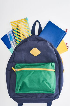 Blue with green pocket schoolbag with notepads and pencil case isolated on white