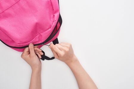 cropped view od schoolkid zipping bright pink schoolbag isolated on white Banco de Imagens