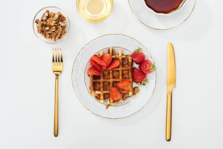 top view of served breakfast with waffle and strawberries on plate, honey and nits in bowls, cup of tea near fork and knife on white