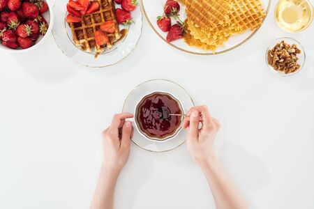 cropped view of woman holding teaspoon and cup of tea near plates with strawberries and waffles on white Stock fotó
