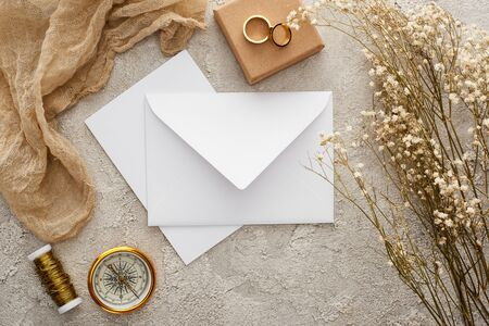 top view of envelope near beige sackcloth, golden compass and wedding rings on textured surface