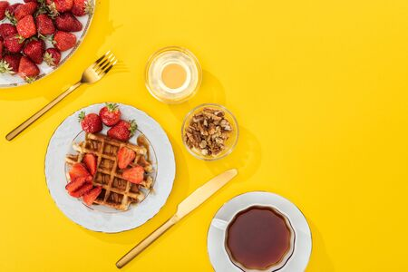 top view of served breakfast with fresh strawberries on yellow