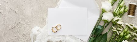 panoramic shot of golden rings on blank card near envelope on white cheesecloth and eustoma flowers on textured surface Stock Photo