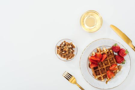 flat lay with crispy waffles and strawberries on plate near bowls on white Stockfoto