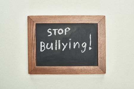 top view of chalkboard in wooden frame with stop bullying lettering on grey background