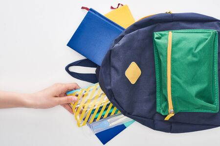 Cropped view of schoolgirl taking yellow pencil case from blue schoolbag with notepads isolated on white
