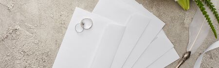 panoramic shot of wedding rings on envelopes near quill pen on textured surface