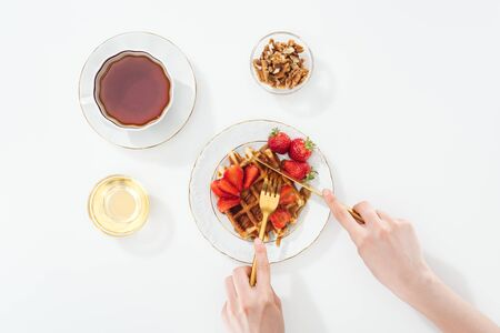 cropped view of woman cutting waffle on plate near cup with tea and bowl on white