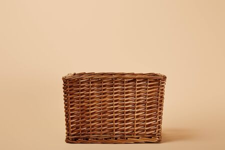 natural brown wicker basket on beige background
