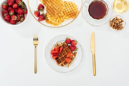 top view of served breakfast with waffles and strawberries on white