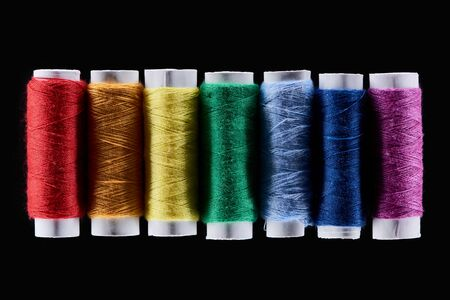 top view of bright and colorful threads isolated on black