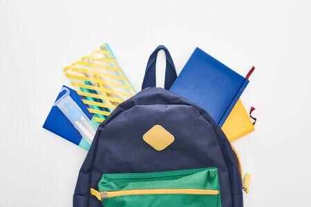 Blaue Schultasche mit verschiedenen Schulmaterialien isoliert auf weiß