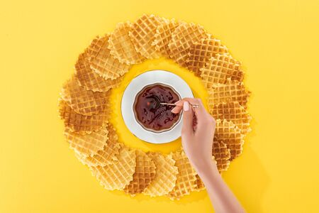 cropped view of woman holding teapot in cup of tea rounded by waffles on yellow