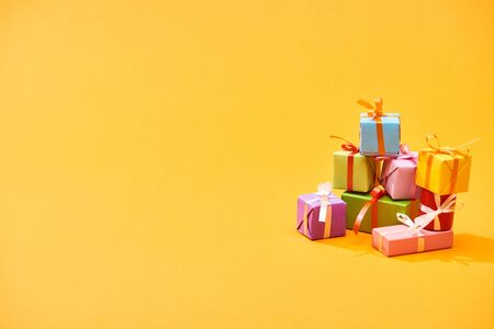 stack of colorful festive boxes on bright orange background