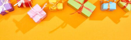 top view of festive wrapped gifts on bright orange background, panoramic shot