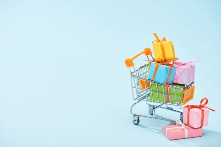 festive wrapped presents in shopping cart on blue background with copy space