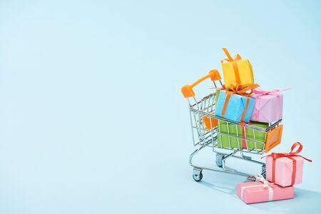 festlich verpackte Geschenke im Einkaufswagen auf blauem Hintergrund mit Kopierraum