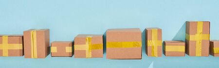 panoramic shot of miniature postal boxes on blue background