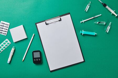 top view of pencil on folder with blank paper rounded by various medical supplies on green surface Zdjęcie Seryjne