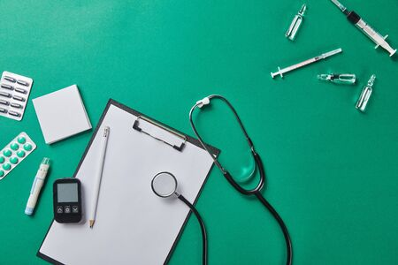 top view of various medical supplies near folder and stethoscope on green surface Zdjęcie Seryjne