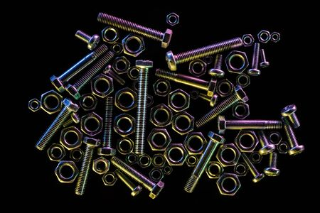top view of scattered steel bolts and nuts isolated on black with copy space