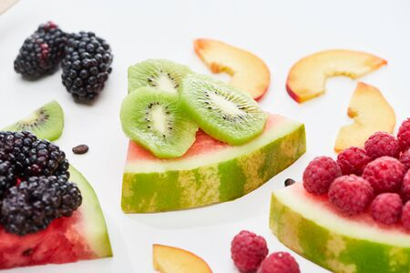 delicious dessert with watermelon, kiwi and berries on white background