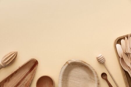 top view of wooden plates, spoons and hand juicer on beige background