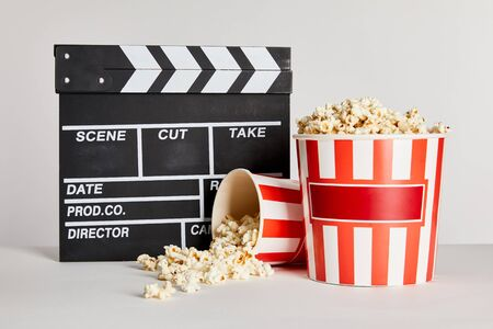 tasty popcorn in striped buckets near clapper board isolated on grey