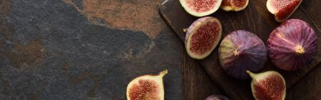 top view of figs and wooden cutting boards on stone background, panoramic shot