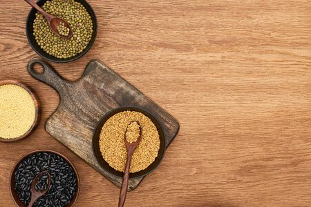 top view of cutting board with bowls with black beans, maash, couscous and buckwheat on wooden surface Zdjęcie Seryjne